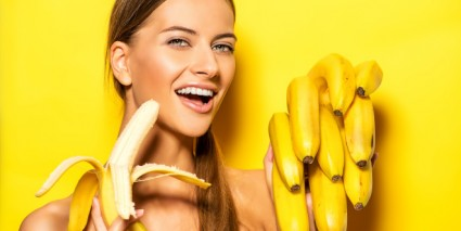 Beautiful young woman with bananas. Tropical fruits. Summer conc