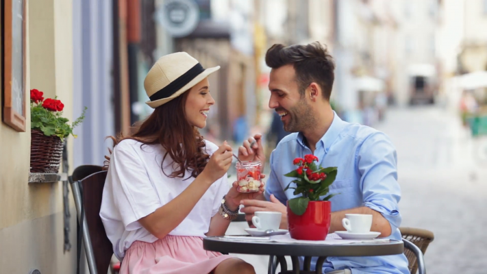 happy-couple-eating-desserts-together-at-outdoors-cafe_n1ov4yy2__F0000