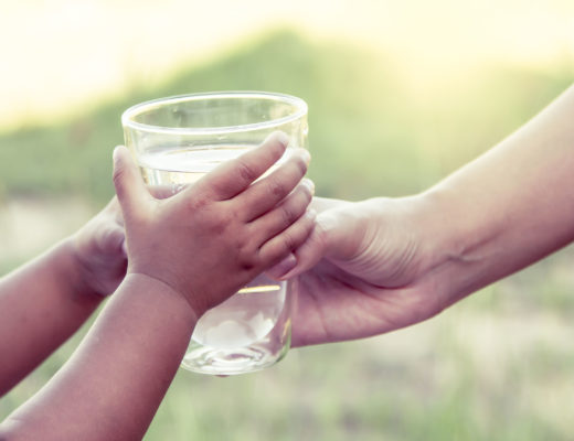 46793015 - woman hand giving glass of fresh water to child in the park,vintage color filter